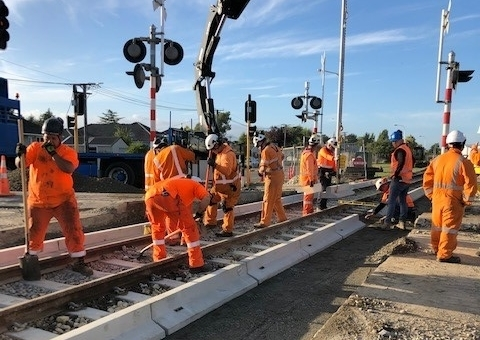 People in full safety gear working on the level crossing at Northcote Road.